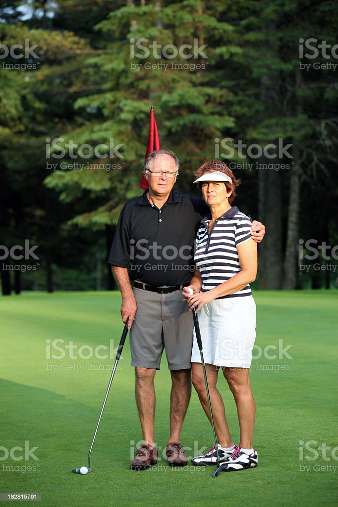 Senior Couple Playing Golf on Putting Green royalty-free stock photo