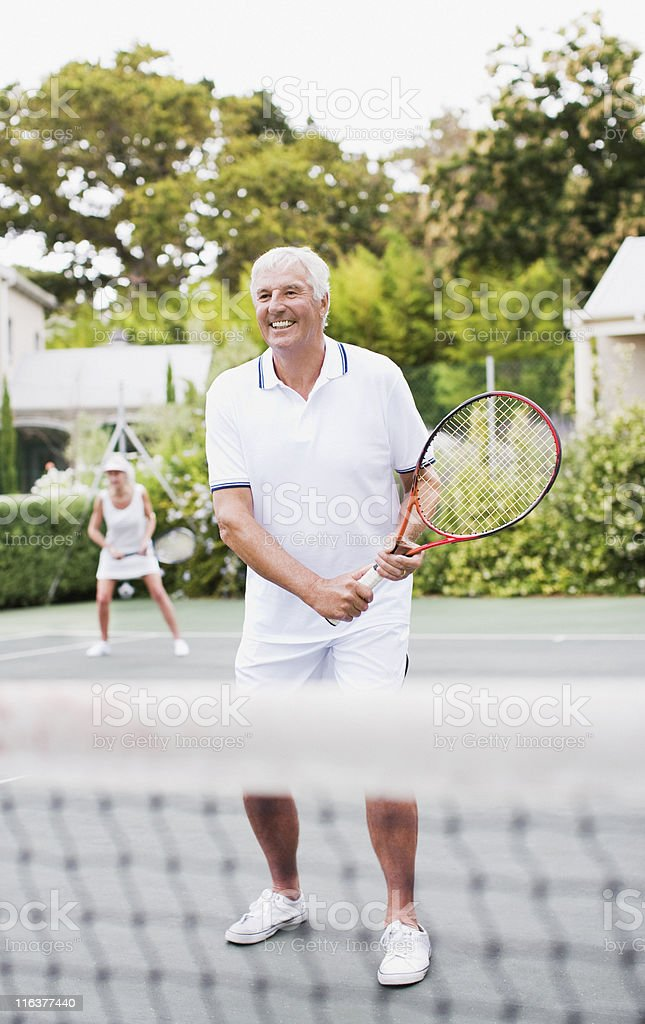 Senior couple playing tennis stock photo