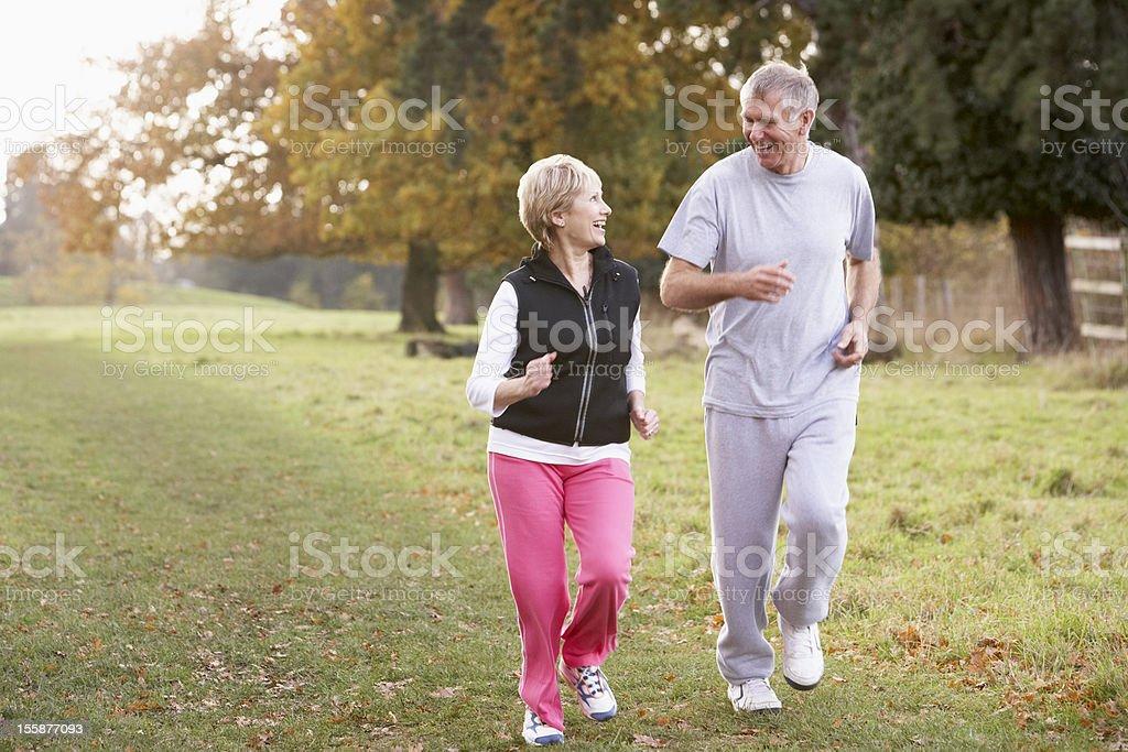 Senior Couple Power Walking In The Park stock photo