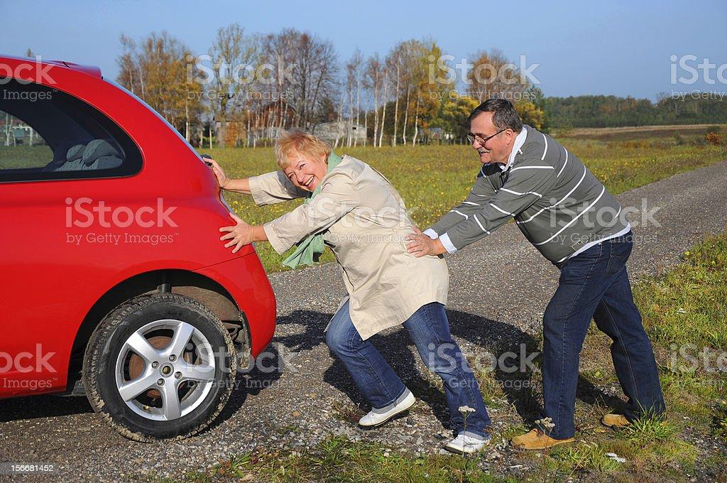 Senior couple pushing car stock photo