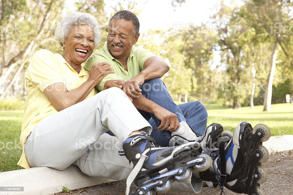 Senior Couple Putting On In Line Skates stock photo