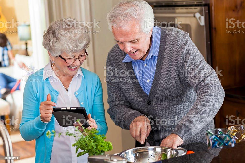 Senior couple read recipe from digital tablet stock photo