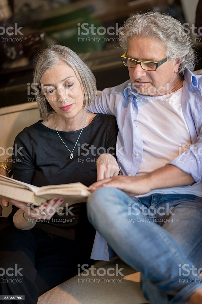 Senior couple reading a book together stock photo