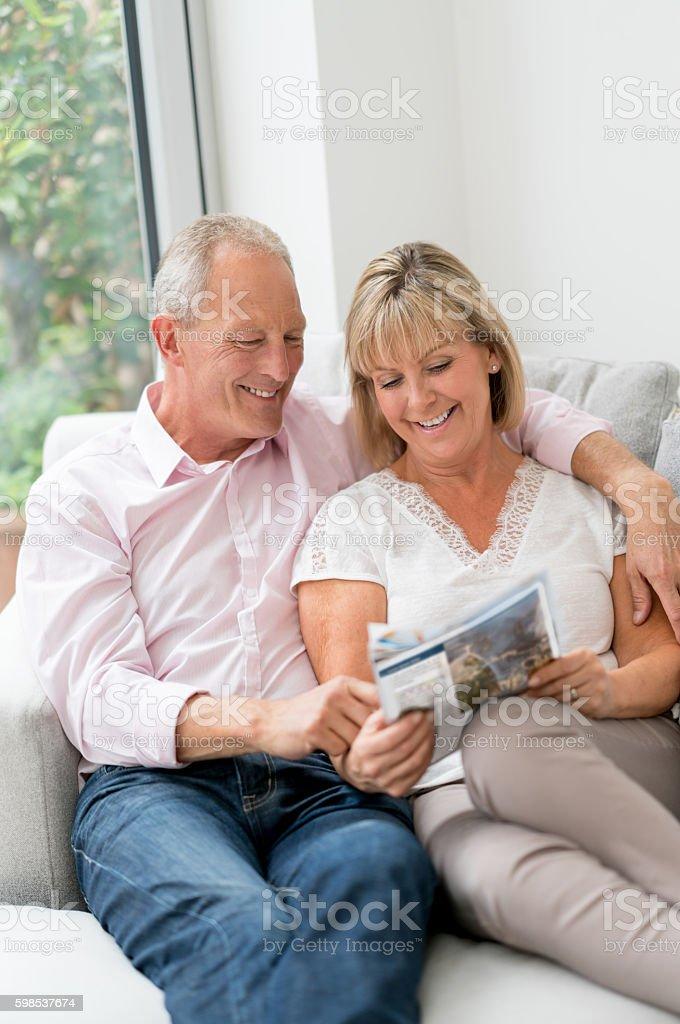 Senior couple reading a magazine at home stock photo