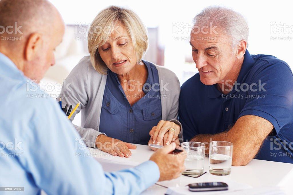 Senior couple reading investment plans royalty-free stock photo