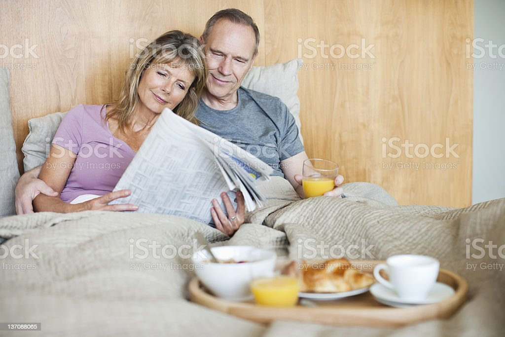 Senior couple reading newspaper and having breakfast in bed royalty-free stock photo