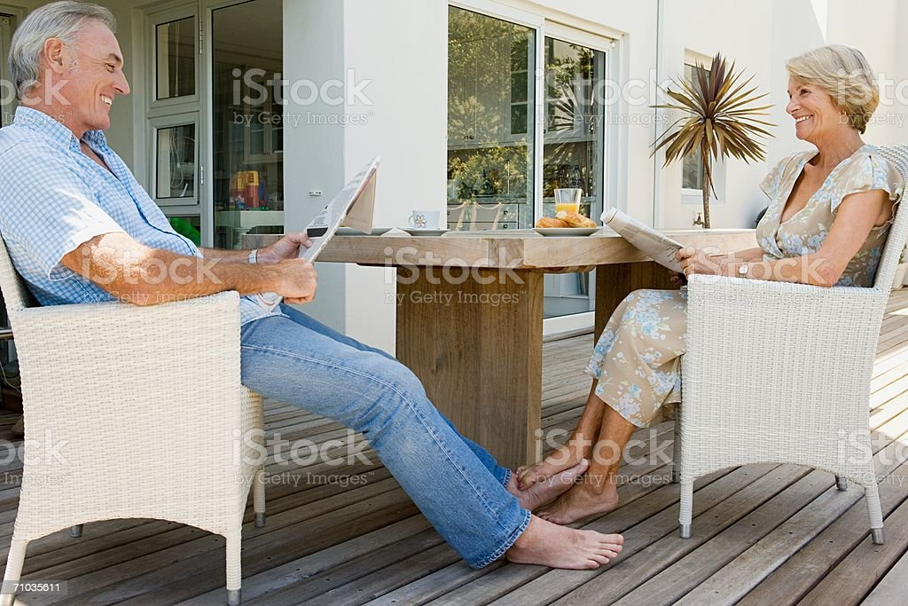 Senior couple reading newspapers stock photo