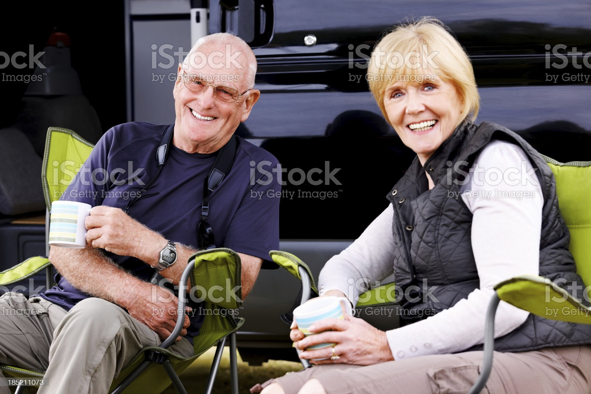 Senior couple relaxing around camper van royalty-free stock photo