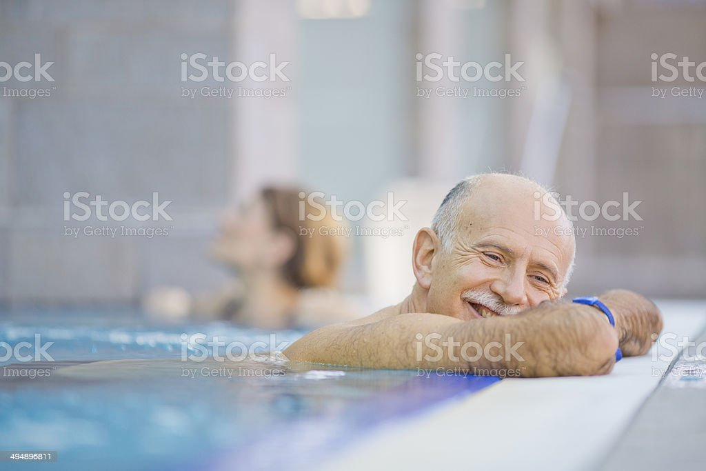 senior couple  relaxing in  hotel pool stock photo