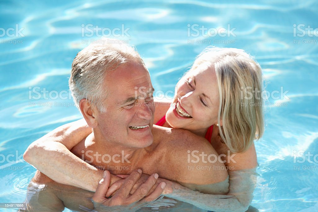 Senior Couple Relaxing In Swimming Pool Together royalty-free stock photo