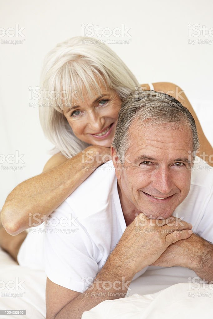 Senior Couple Relaxing On Bed royalty-free stock photo