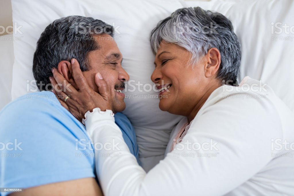 Senior couple relaxing together on bed in bedroom royalty-free stock photo