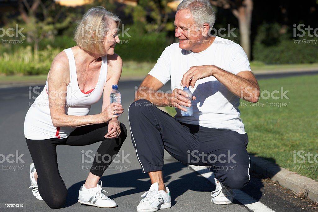 Senior Couple Resting And Drinking Water After Exercise royalty-free stock photo