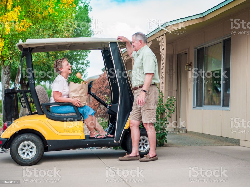 Senior couple returning home after shopping stock photo