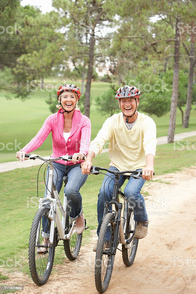 Senior couple riding bicycles in park royalty-free stock photo
