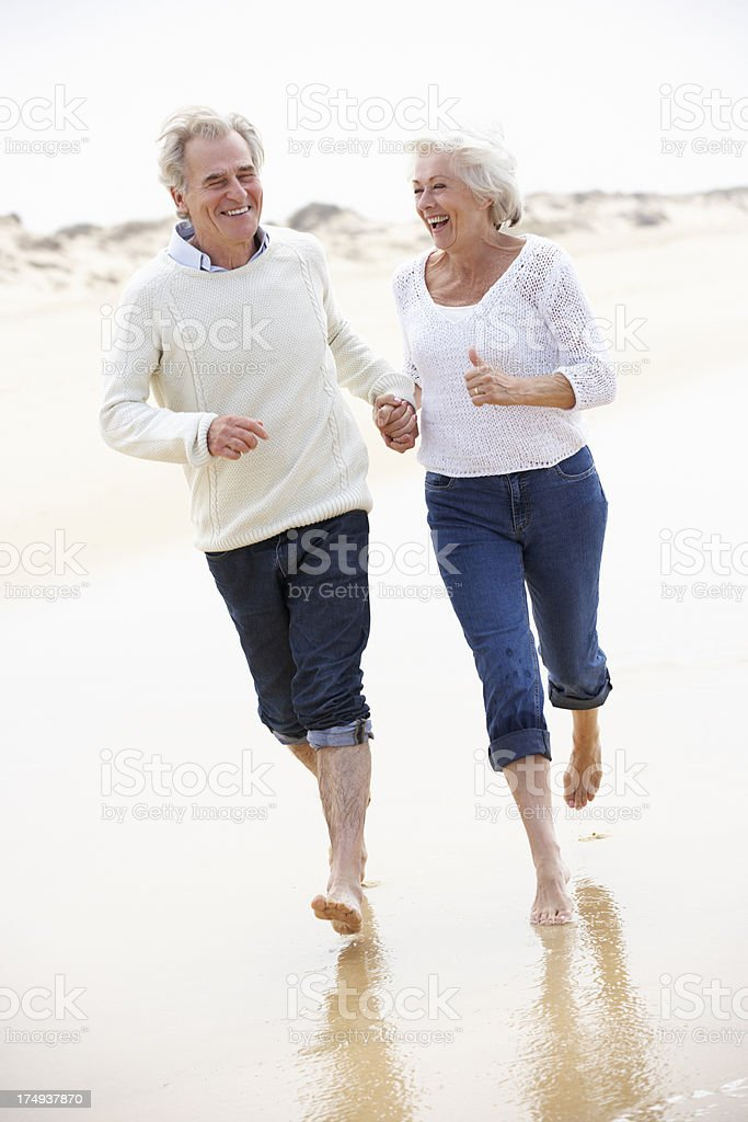 Senior Couple Running Along Beach Together royalty-free stock photo