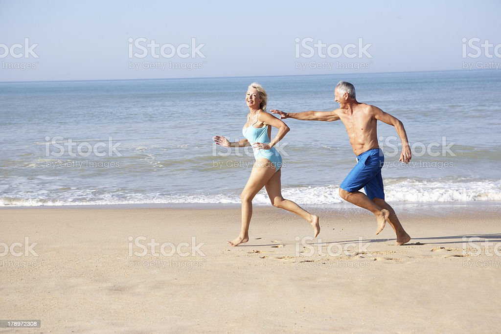 Senior couple running on beach royalty-free stock photo