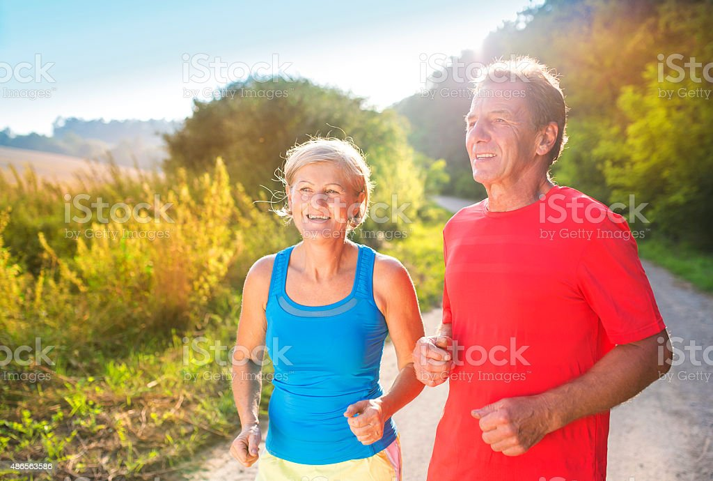 Senior couple running stock photo