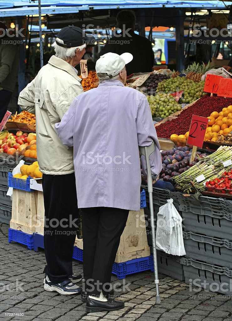 Senior couple seen from behind at farmers market. royalty-free stock photo