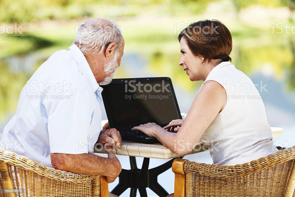 Senior couple share a laptop computer in garden setting royalty-free stock photo