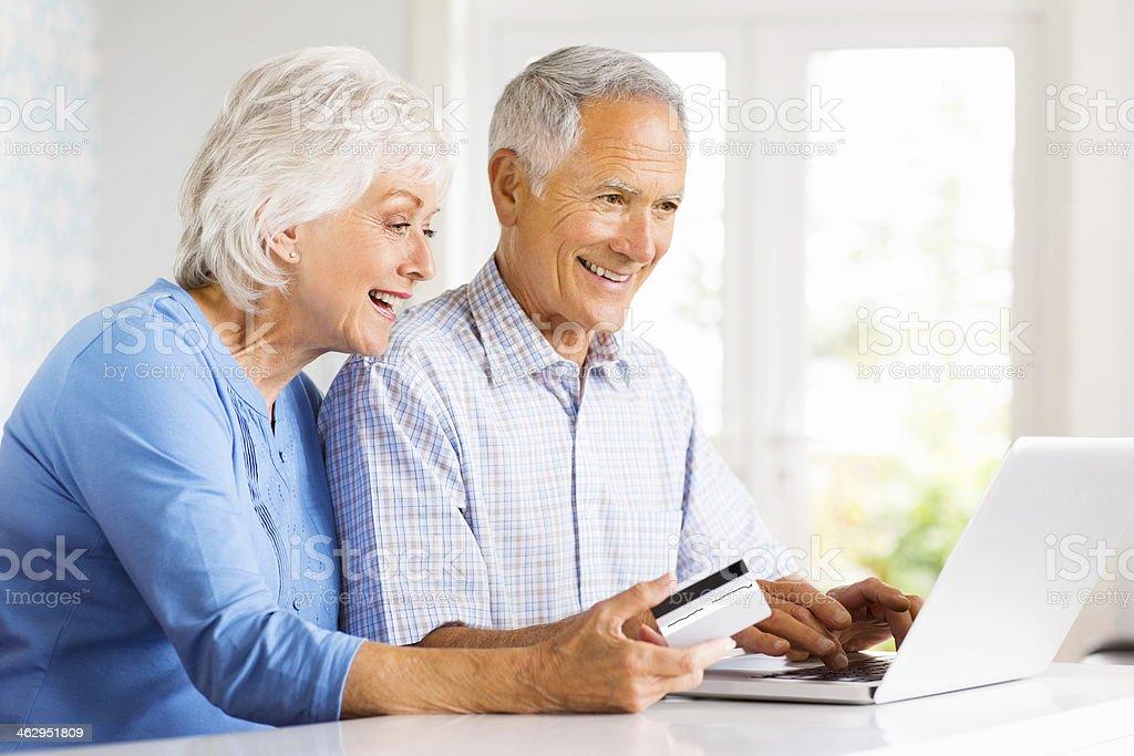 Senior Couple Shopping On Internet At Home. stock photo