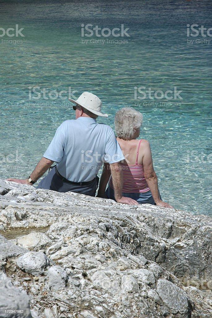 Senior Couple Sits on Rocky Mediterranean Shore royalty-free stock photo