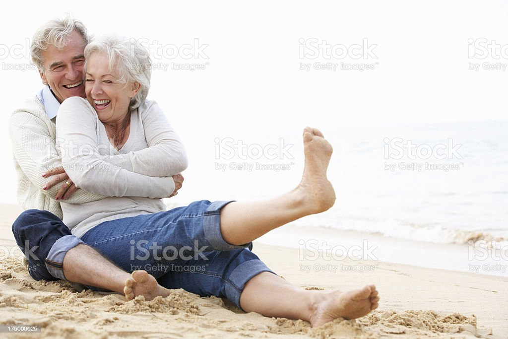 Senior couple sitting and laughing together on the beach stock photo