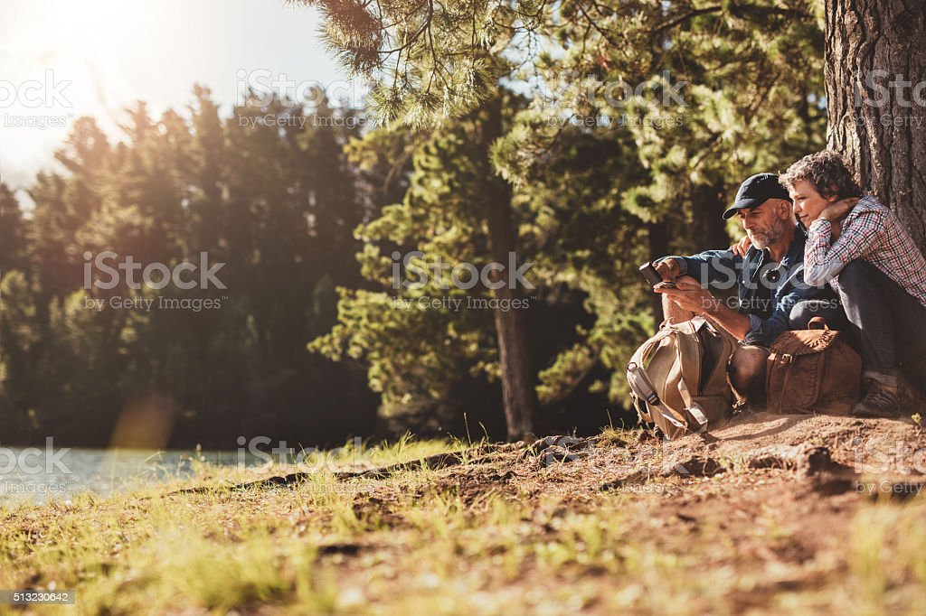 Senior couple sitting by a lake using compass stock photo
