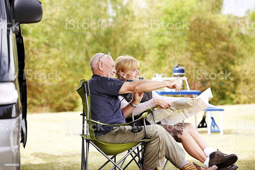 Senior couple sitting by camper van reading a map royalty-free stock photo