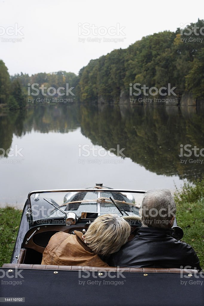 Senior couple sitting in antique car, looking out at pond royalty-free stock photo