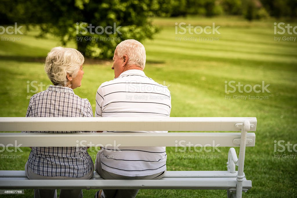 Senior couple sitting in park stock photo