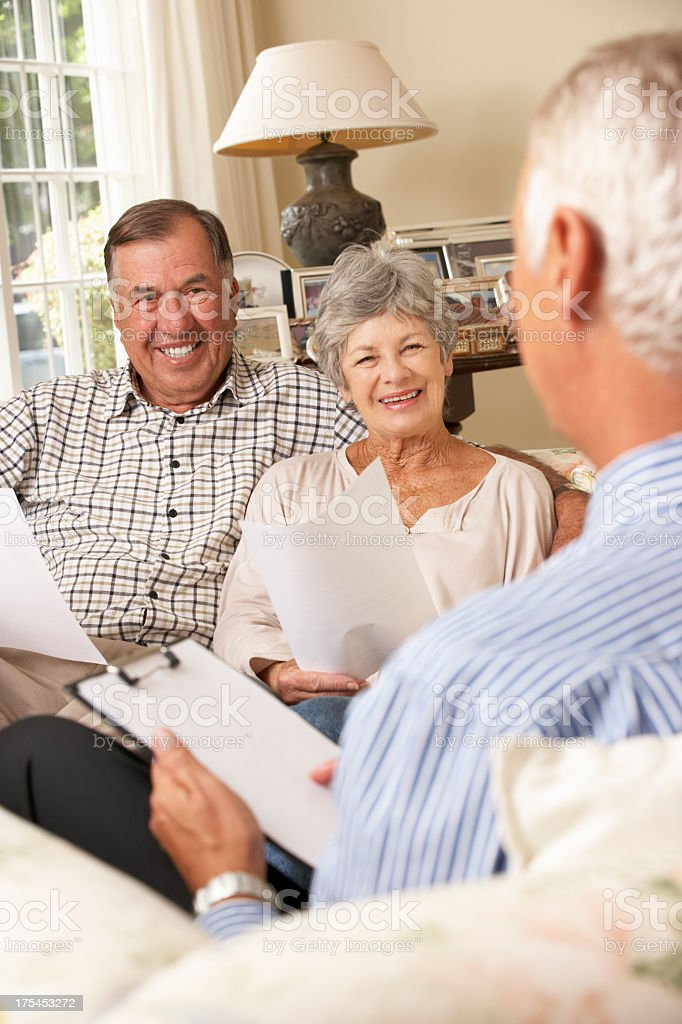 Senior couple sitting in their home talking with an advisor royalty-free stock photo