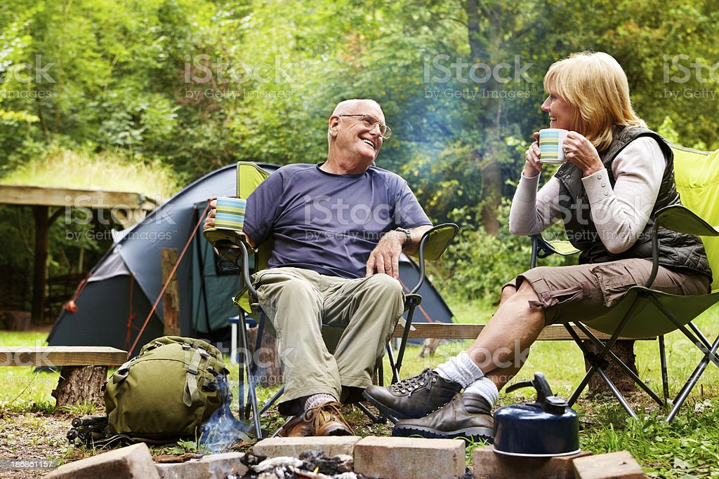 Senior Couple Sitting Near a Campfire royalty-free stock photo