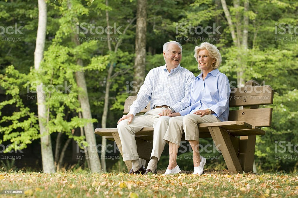 Senior Couple Sitting On A Park Bench royalty-free stock photo