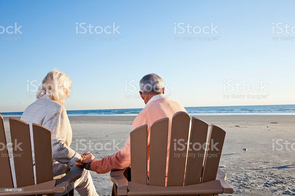 Senior couple sitting on beach royalty-free stock photo
