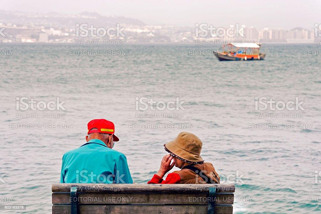 Senior couple sitting on bench overlooking Hiroshima Bay,Japan stock photo