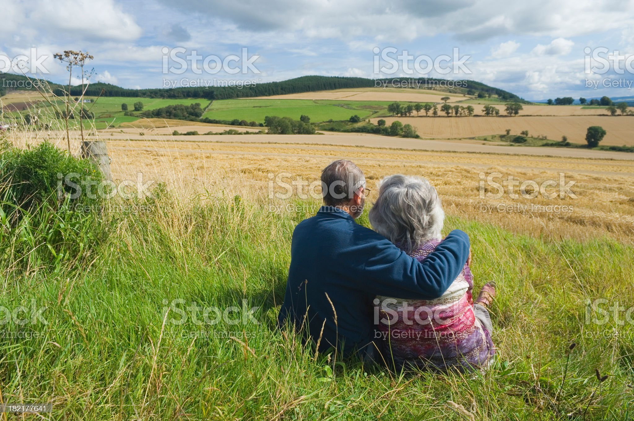 A senior couple sitting on grass looking out at a dry field royalty-free stock photo