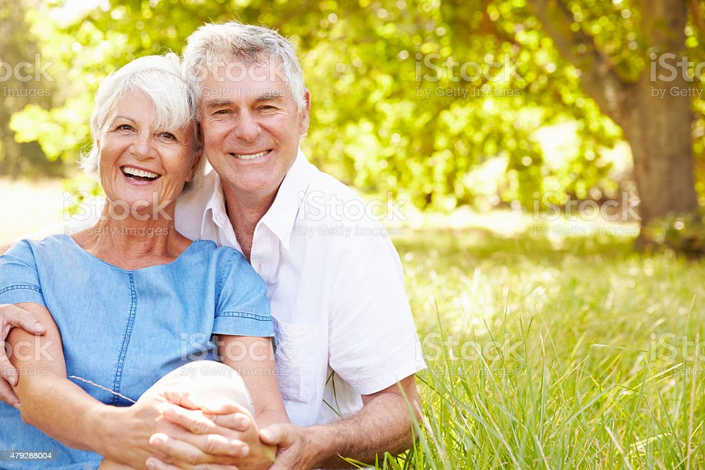 Senior couple sitting on grass together relaxing stock photo
