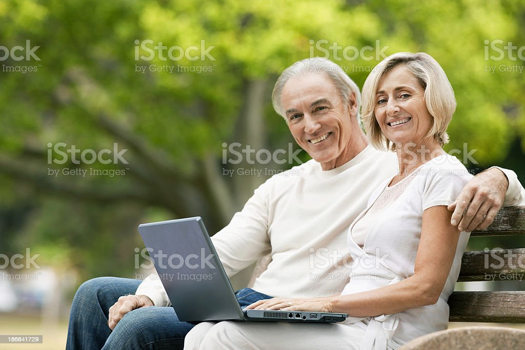Senior Couple Sitting on Park Bench With Laptop royalty-free stock photo