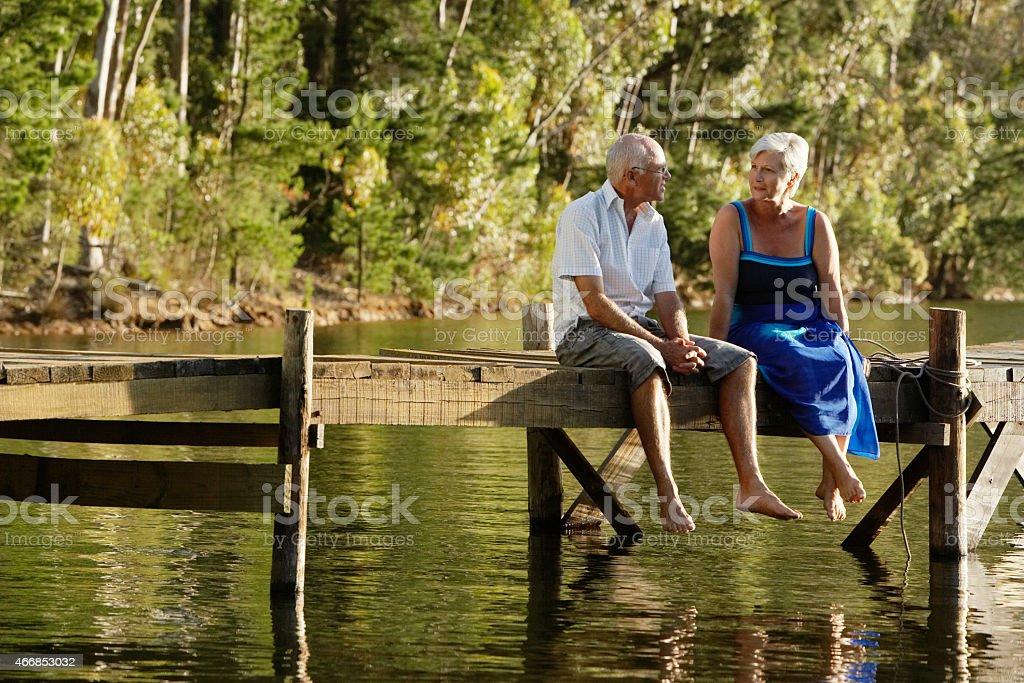 Senior Couple Sitting On Pier At Lake stock photo