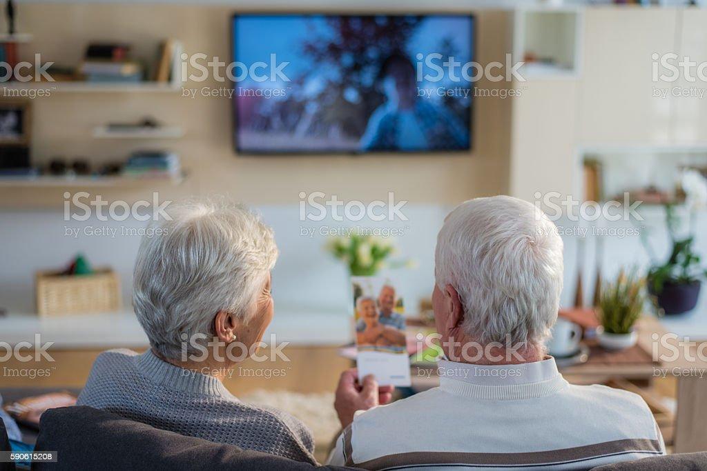 Senior couple sitting on sofa stock photo