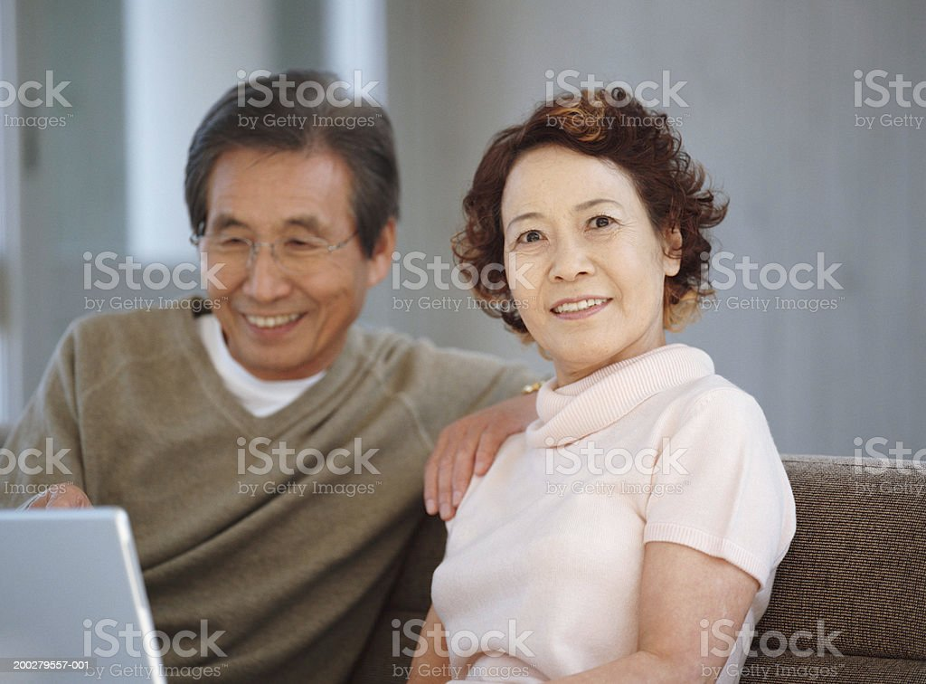 Senior couple sitting on sofa using laptop, portrait of woman stock photo
