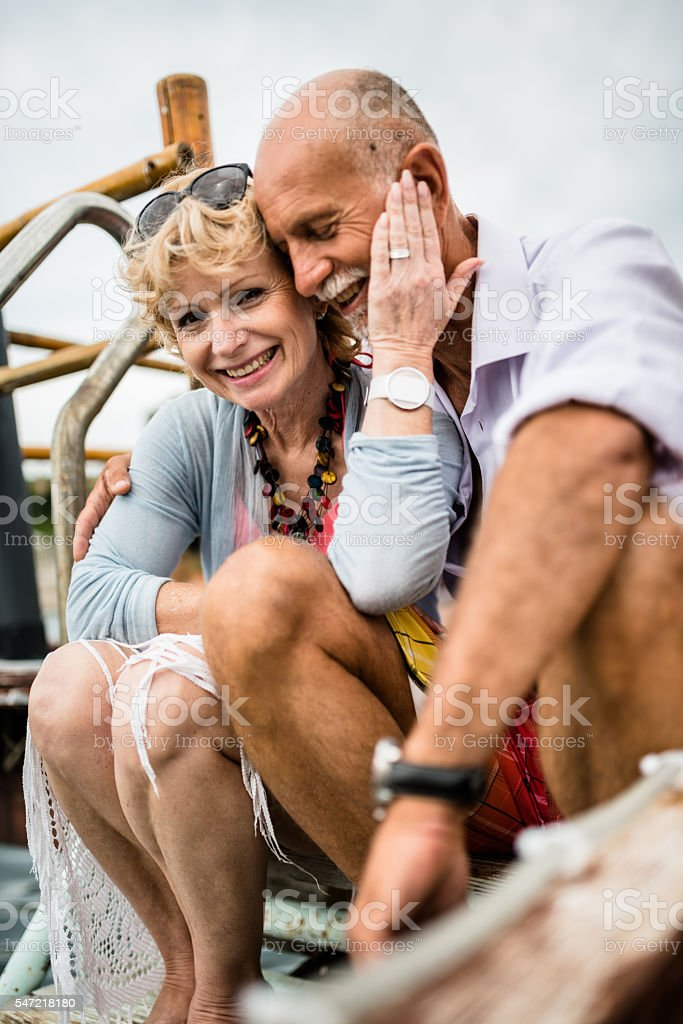 senior couple sitting on the jetty relaxing stock photo