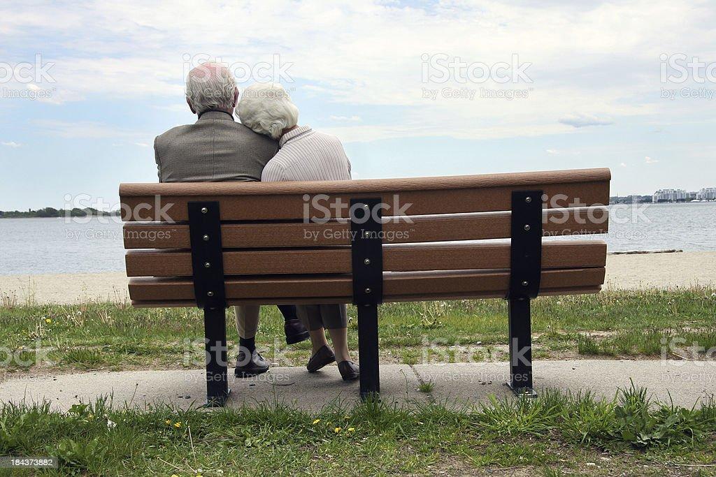 Senior Couple Sitting On The Park Bench royalty-free stock photo