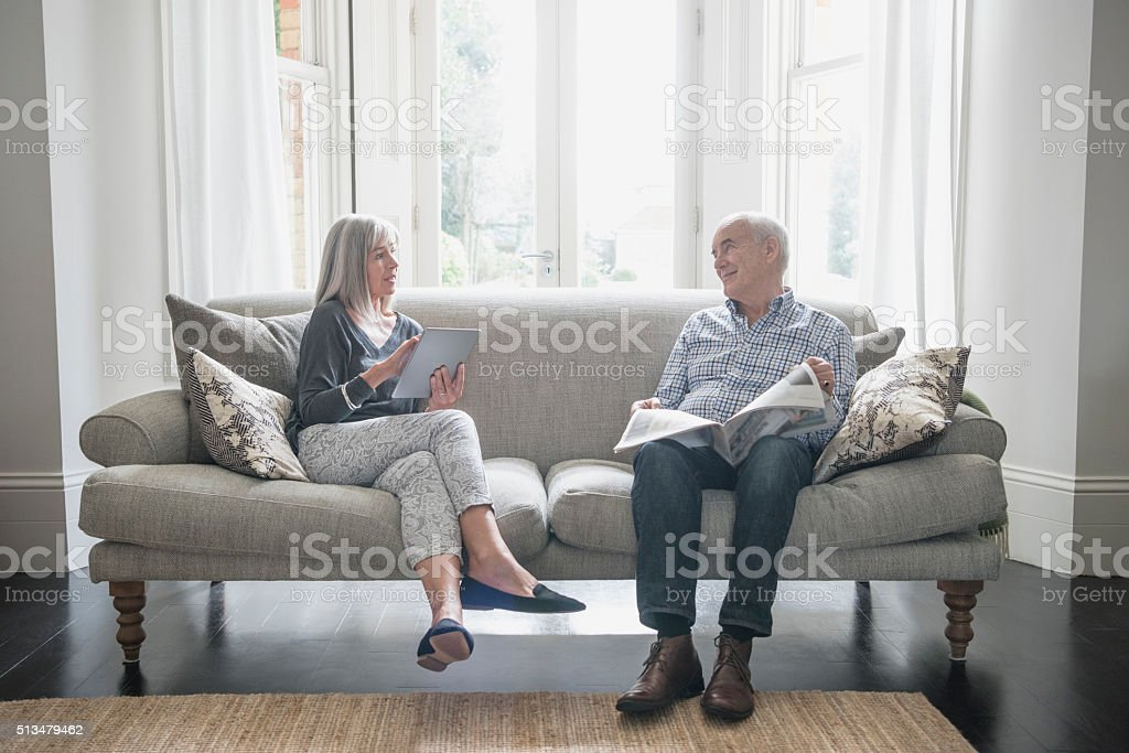Senior couple sitting on the sofa at home, talking stock photo