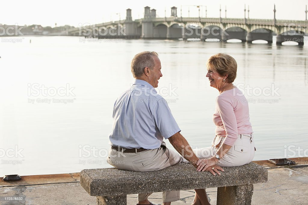 Senior couple sitting on waterfront stock photo