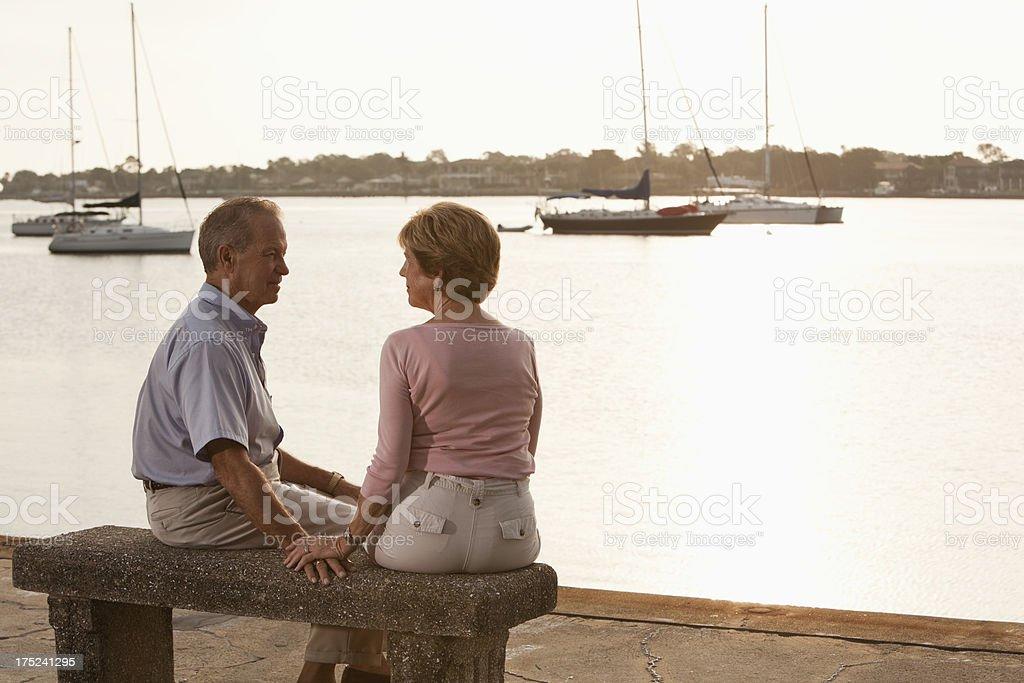 Senior couple sitting on waterfront royalty-free stock photo