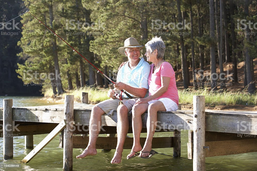 Senior couple sitting on wooden dock and fishing stock photo
