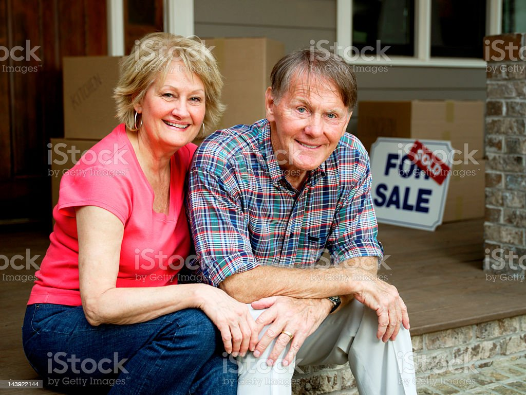 Senior Couple Sitting Outside House With For Sale Sign royalty-free stock photo