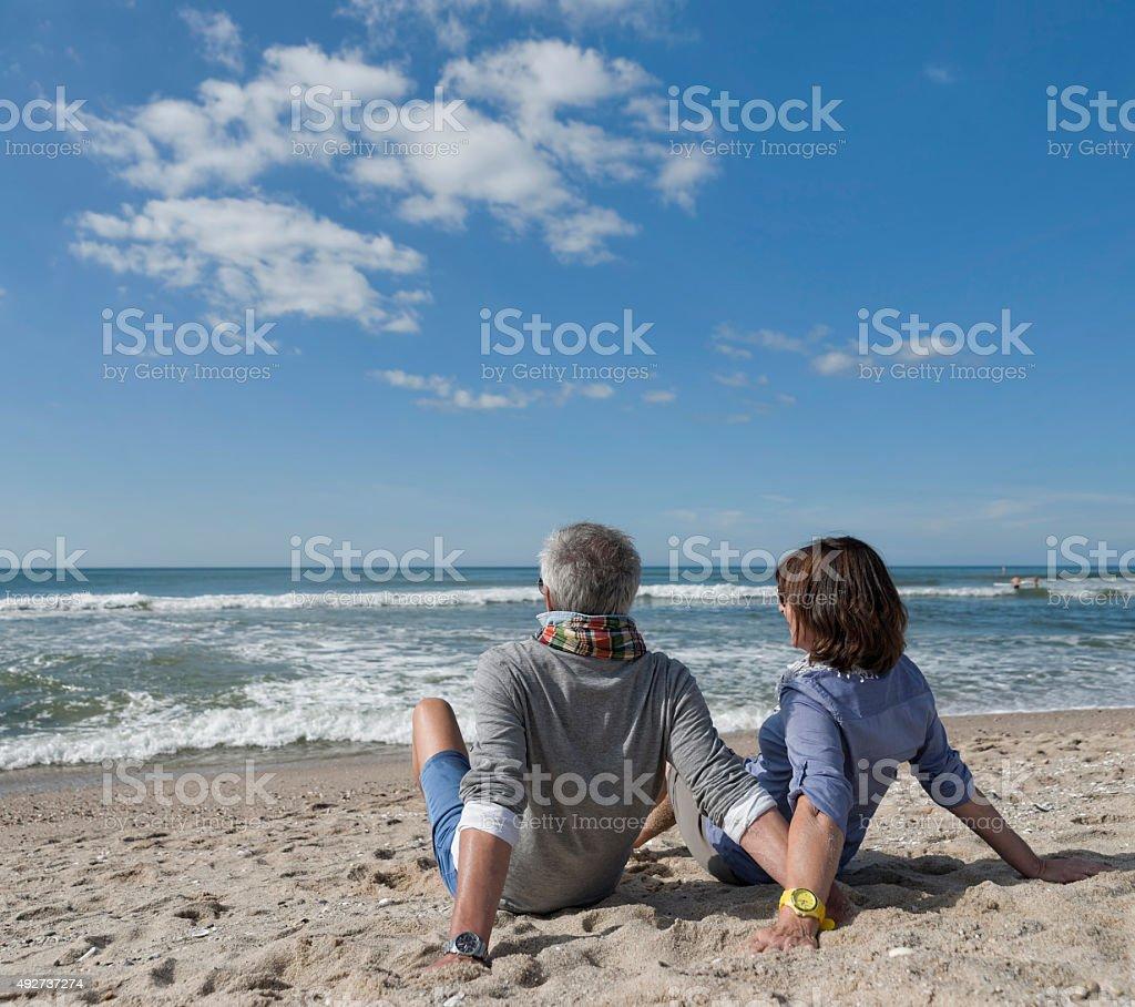 Senior couple sitting relaxed on beach of Sylt stock photo